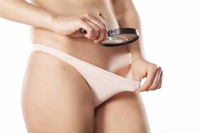 Chica examinando su vagina con lupa