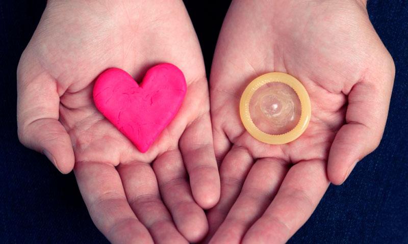 Corazón con preservativo en las manos de una persona