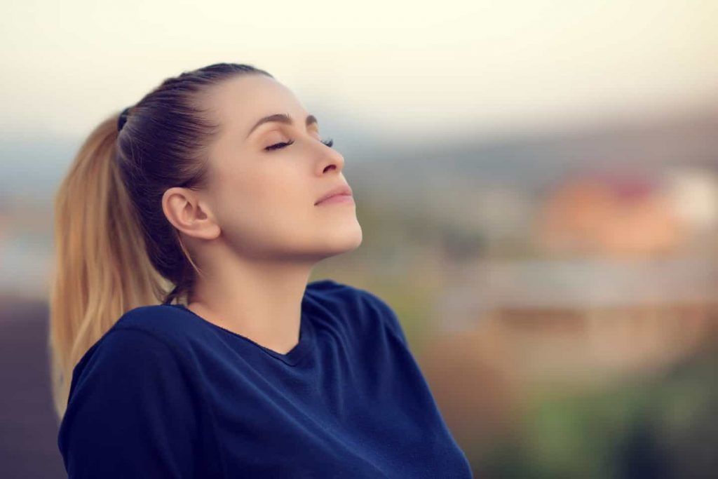 Chica respirando con ojos cerrados