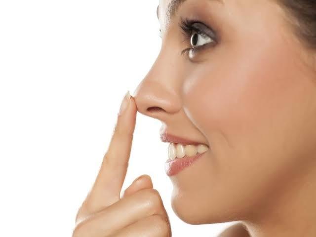 Chica tocando su nariz