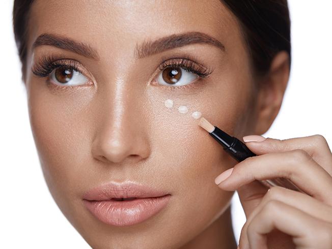 Chica con corrector de ojos siguiendo tips de maquillaje