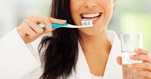 Mujer cepillándose los dientes sanos