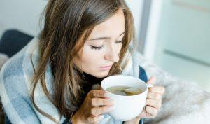Mujer tomando té para el dolor de estómago